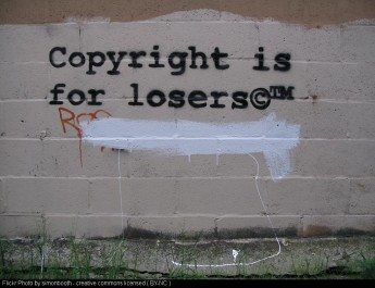 graffiti on a wall saying 'copyright is for losers