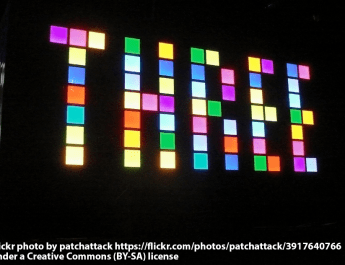 THREE written in coloured square lights on a building