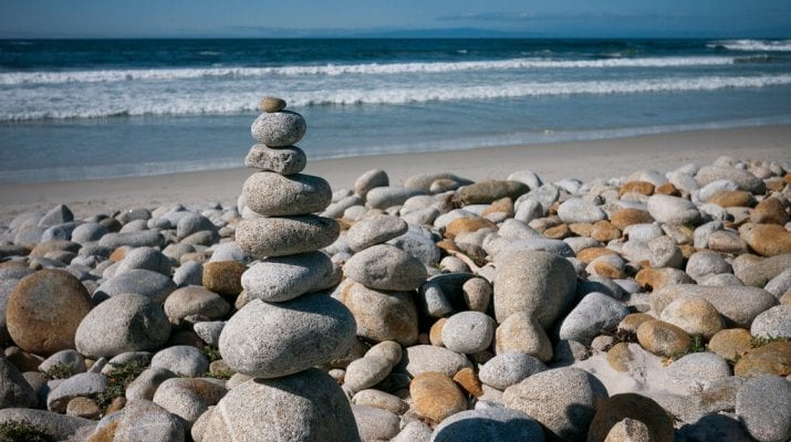 A photograph of a sunny beach with pebbles in the foreground. Among the pebbles is a stack of 8 pebbles balancing one on top of the other.