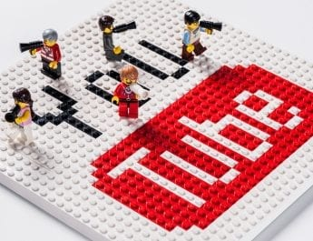 5 Lego mini figures on a large Lego tile that has the words You and Tube on it in the YouTube logo colours.